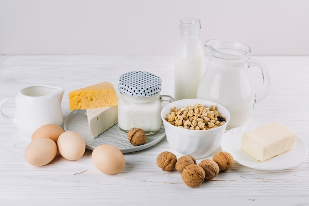 Cuenco de cereales; leche; huevos; queso y nueces sobre fondo blanco con textura Foto gratis