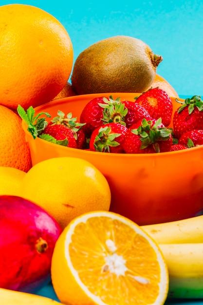 Cuenco de fresas; naranja; kiwi y plátano sobre fondo azul Foto gratis
