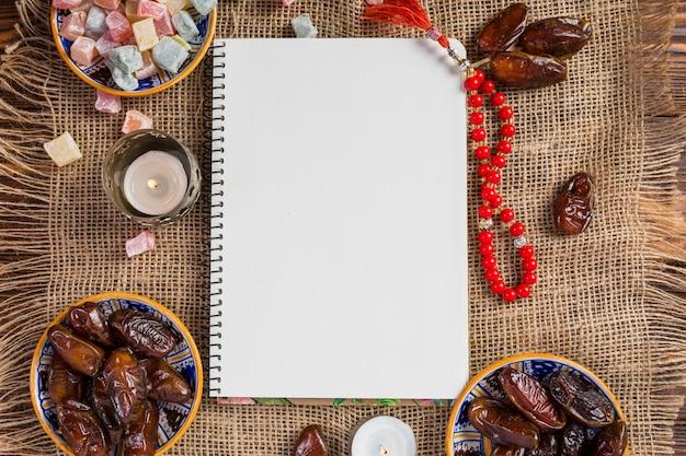 Cuenco turco de dátiles jugosos; deleite lukum con una página en blanco en blanco y cuentas rojas santas sobre tela de yute Foto gratis