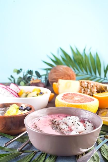 Cuencos acai batidos rojos o rosados cubiertos con semillas de chaya y pitaya frescas en hoja de palma en el fondo de piedra, espacio de copia Foto Premium