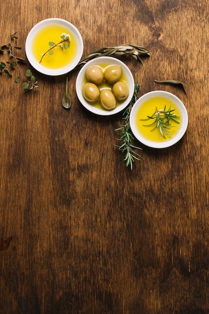 Cuencos de aceite de oliva con romero y vista superior del espacio de copia Foto gratis