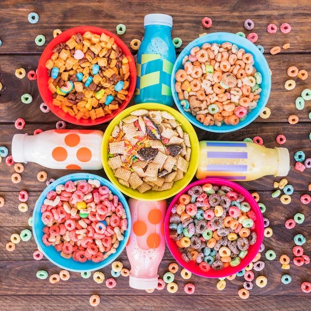 Cuencos brillantes de cereales con botellas de leche en la mesa Foto gratis
