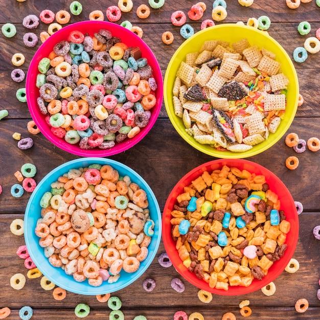 Cuencos brillantes con cereales en mesa de madera Foto gratis