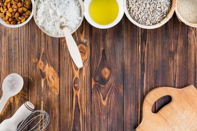 Cuencos de ingredientes para hornear en la mesa de madera oscura Foto gratis