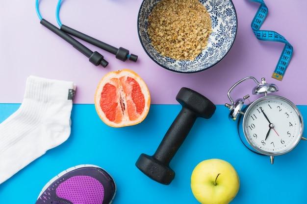 Cuerda saltar; cinta métrica; calcetín; pesa; zapatos; manzana; fruta de naranja a la mitad; reloj despertador en doble fondo Foto gratis