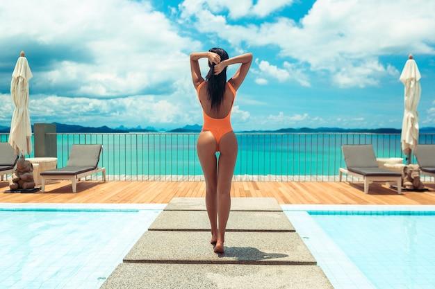 Cuerpo de verano mujer en traje de baño naranja junto a la piscina con vistas al mar. chica en traje de baño de moda con cuerpo perfecto en el resort de lujo. vista trasera Foto Premium