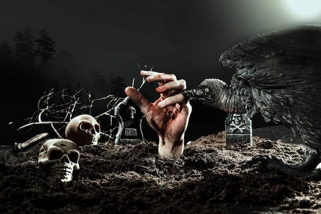 Cuervo espeluznante mordiendo la mano de zombie en el cementerio de halloween Foto gratis