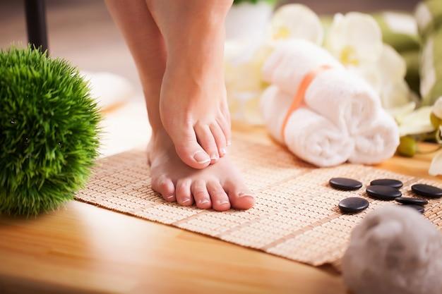 Cuida las piernas de una mujer hermosa en el piso Foto Premium