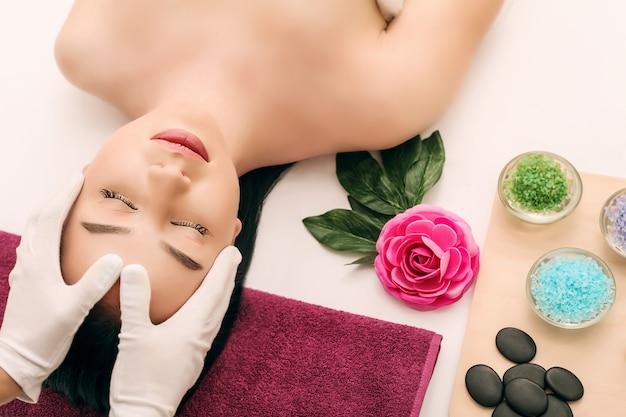 Cuidado del cuerpo. tratamiento de masaje corporal spa. la niña se relaja en el salón de spa Foto Premium