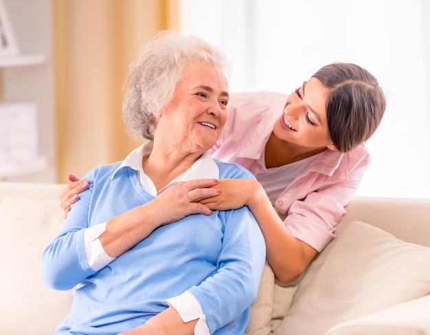 Cuidado de la mujer mayor en casa sentado en el sofá. Foto Premium