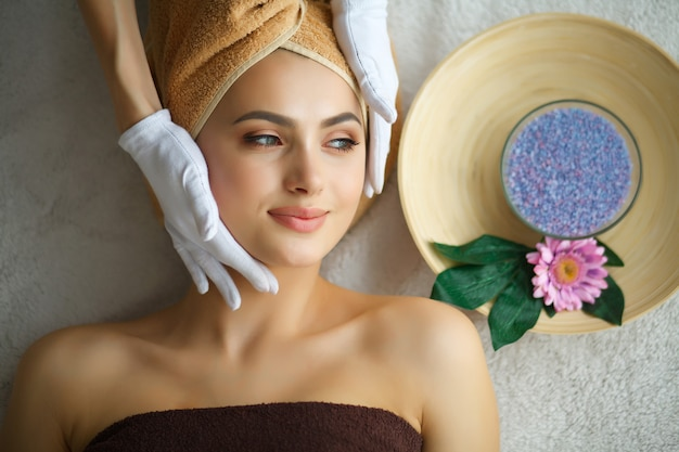Cuidado de la piel y el cuerpo. primer plano de una mujer joven recibiendo tratamiento de spa en el salón de belleza. spa masaje facial. tratamiento de belleza facial. salón de spa Foto Premium
