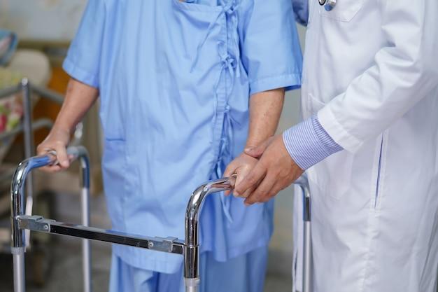 Cuide y ayude al paciente mayor de la mujer a caminar con el caminante en el hospital. Foto Premium