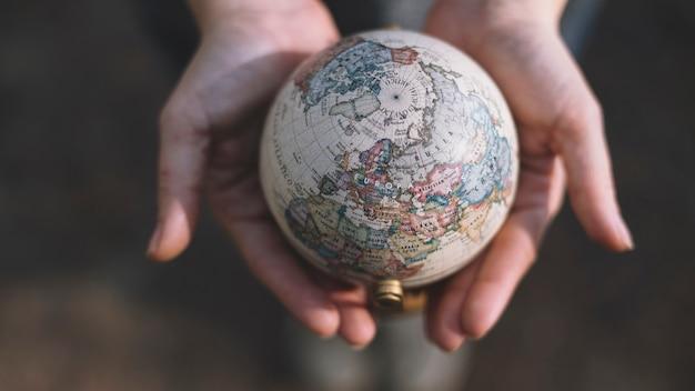 Cultive las manos sosteniendo el globo Foto gratis