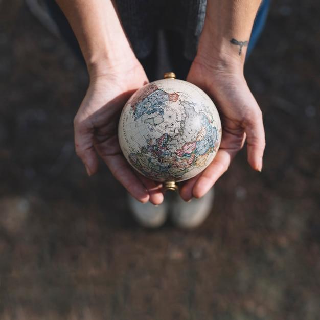 Cultive las manos sosteniendo el globo Foto Premium