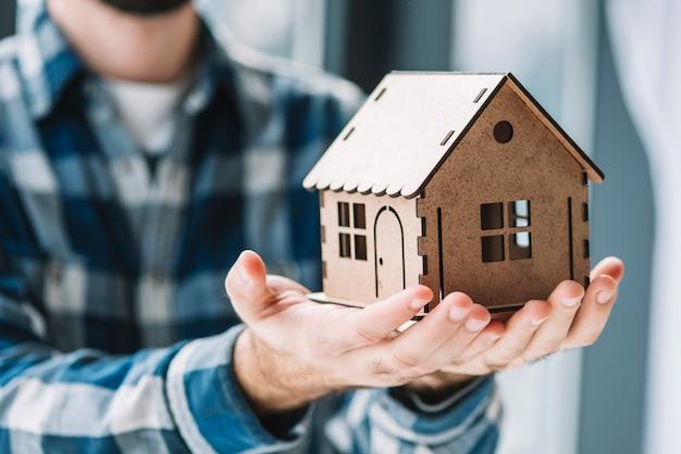Cultivo hombre sosteniendo casa de juguete Foto gratis