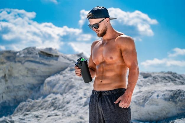 Culturista descansando y bebiendo batido de proteínas después del ejercicio. deporte al aire libre Foto Premium