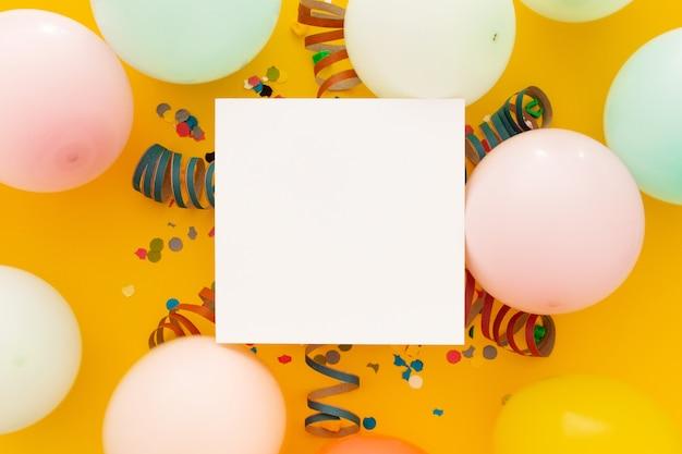 Cumpleaños con confeti y globos de colores en amarillo Foto gratis