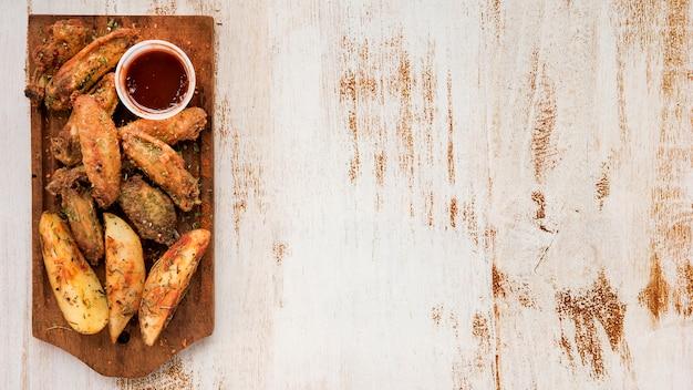 Cuñas de patata y alitas asadas con salsa. Foto gratis