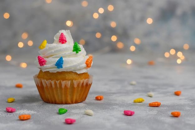 Cupcake de navidad con luces de bengala en forma de árbol de navidad y luces encendidas Foto gratis