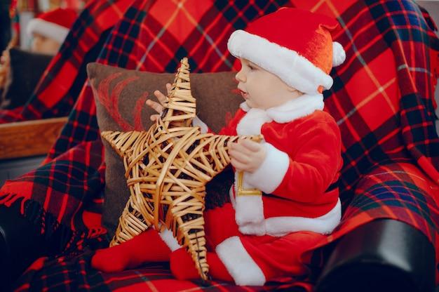 Cutte little boy en casa cerca de decoraciones navideñas Foto gratis