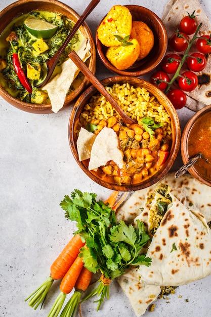 Dal, palak paneer, curry, arroz, chapati, chutney en cuencos de madera sobre la mesa blanca. Foto Premium