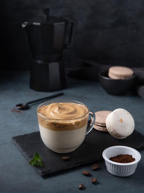 Dalgona café en taza con macarrones sobre fondo amarillo Foto Premium