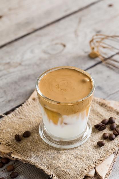 Dalgona café en un vaso sobre una mesa de madera Foto Premium
