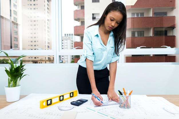 Dama afroamericana con pluma y regla cerca del plan en mesa con equipos Foto gratis