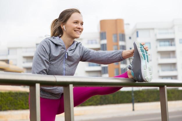 Dama feliz motivada haciendo ejercicio sola al aire libre Foto gratis