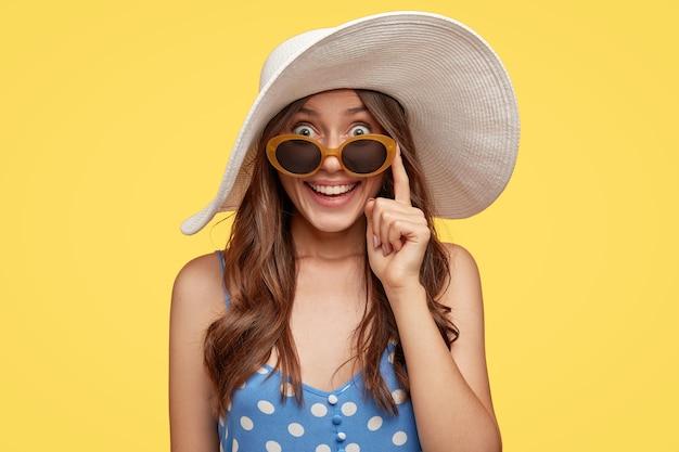 Dama de moda con expresión alegre, usa sombrero blanco y gafas de sol, encuentra un hotel para quedarse durante las vacaciones, lista para ir a la playa, aislada sobre una pared amarilla. concepto de turismo y horario de verano. Foto gratis