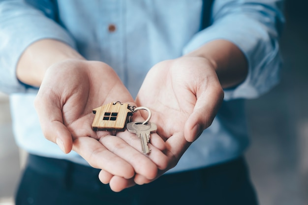 Dando, ofreciendo, demostrando, sosteniendo las llaves de la casa. Foto Premium