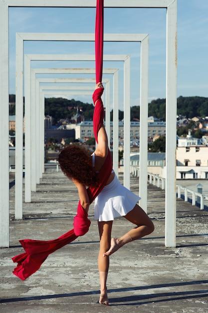 Danza aérea en la azotea, bailarina de seda morena sexy en vestido blanco Foto gratis