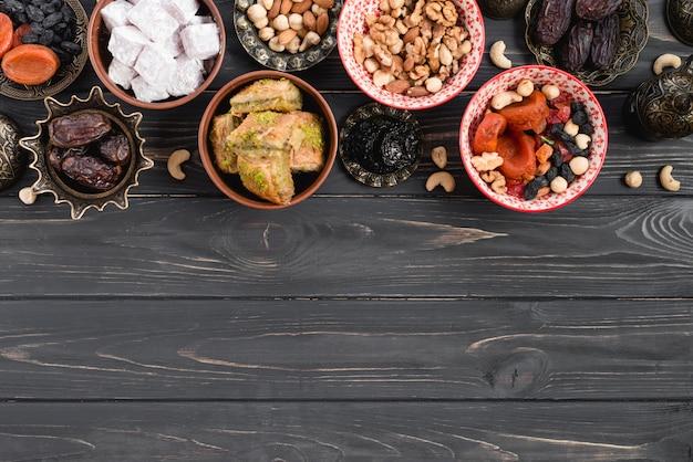 Dátiles orgánicos crudos secos; frutas secas; nueces; lukum y baklava en mesa de madera negra Foto gratis