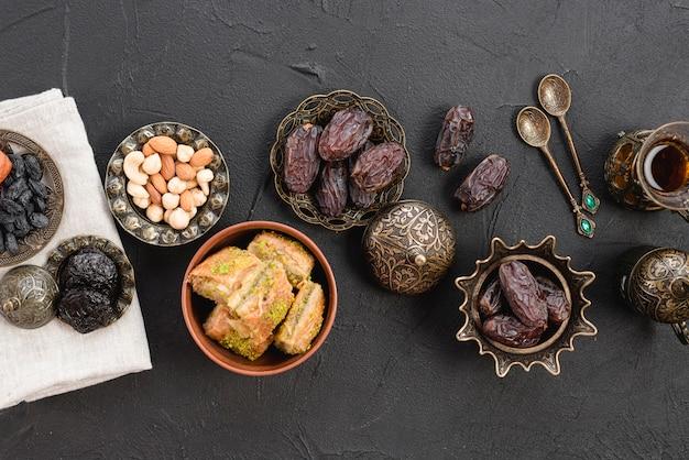 Dátiles orgánicos crudos secos; nueces y baklava en placa de hierro metálico sobre el fondo negro Foto gratis