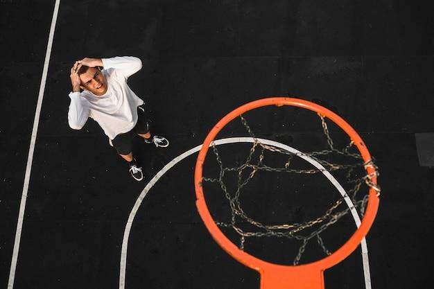 Decepcionado jugador de baloncesto falta aro Foto gratis