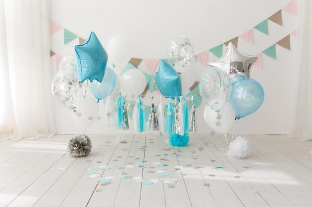 Decoración festiva de fondo para la celebración de cumpleaños con pastel gourmet y globos azules. Foto gratis