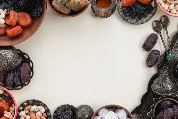 Decoración de fiestas orientales con dátiles frutales; fechas; lukum y nueces sobre fondo blanco con espacio en el centro para escribir el texto Foto gratis