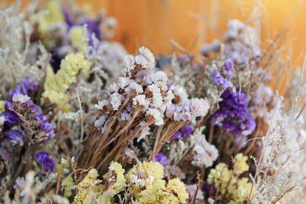 Decoración de flores de colores secos en café sobre fondo amarillo. enfoque selectivo en el centro. Foto Premium