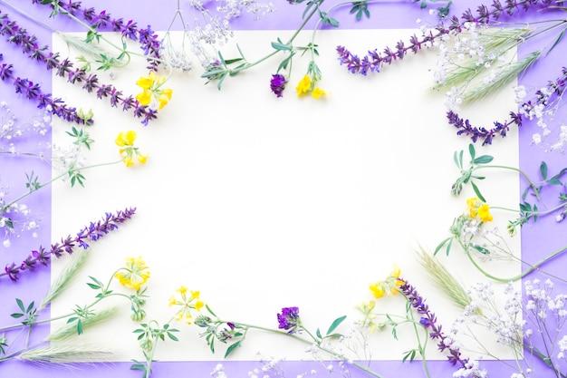 Decoración de flores en papel blanco sobre el fondo púrpura Foto gratis