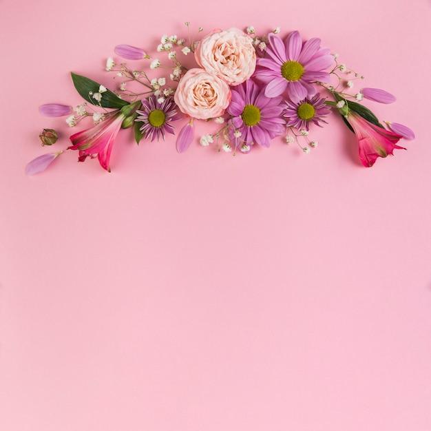 Decoración de flores sobre fondo rosa. Foto gratis