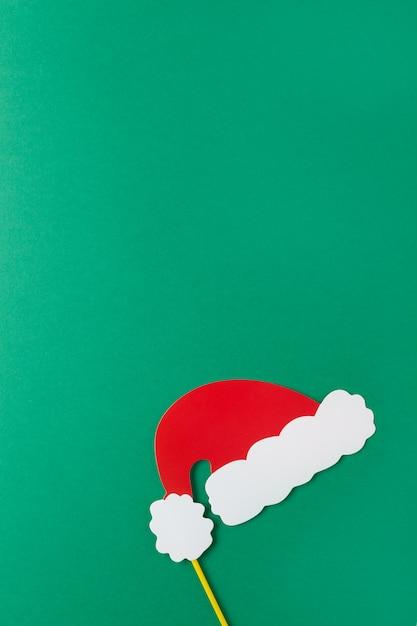 Decoración de navidad, sombrero rojo de papá noel en el palo sobre fondo verde con espacio de copia Foto Premium