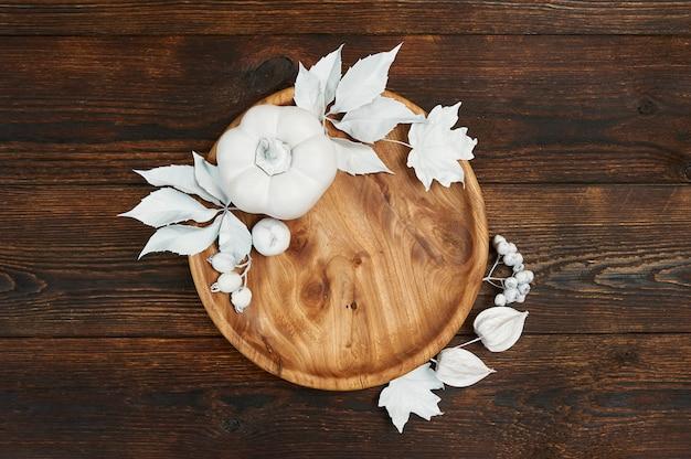 Decoración de otoño con hojas blancas y calabaza con lugar de madera en el fondo de madera de color marrón oscuro. coloque la maqueta para su arte, imagen o letras a mano. composición copia espacio, vista superior. Foto Premium