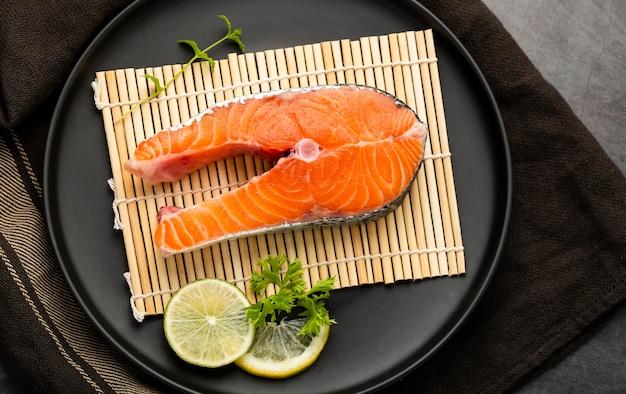 Decoración plana con rodaja de pescado y lima Foto gratis