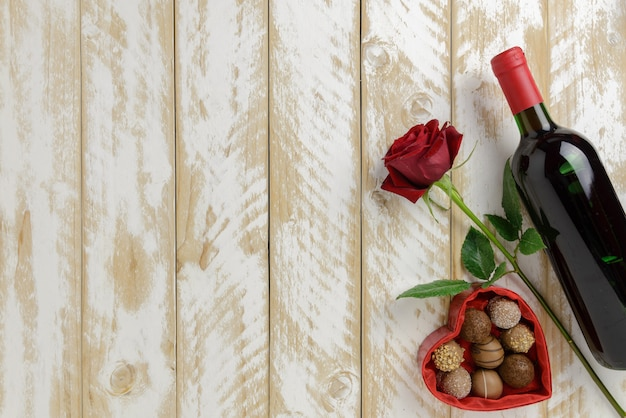 Decoración romántica del día de san valentín con rosas, vino y chocolate sobre un fondo blanco de mesa de madera Foto Premium