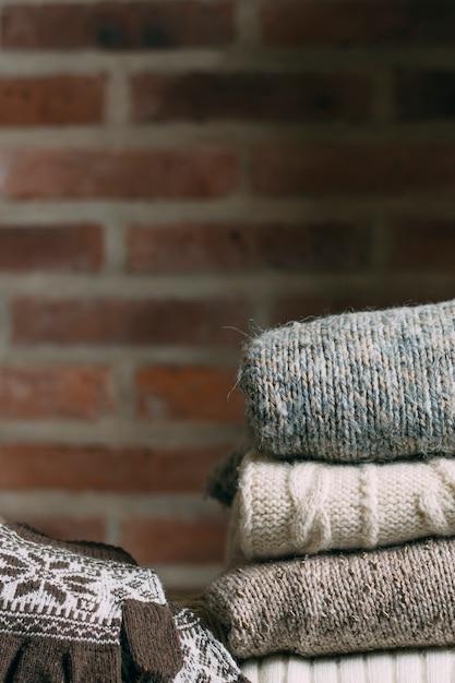 Decoración con ropa abrigada y pared de ladrillo. Foto gratis