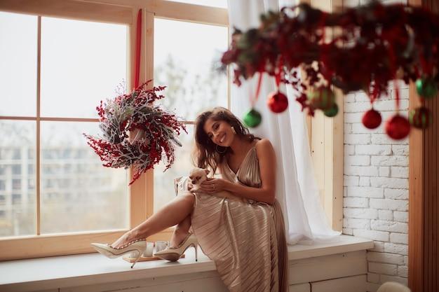 Decoración de vacaciones de invierno. colores cálidos. encantadora y feliz mujer en vestido beige. Foto gratis