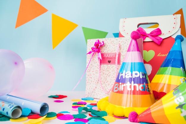 Decoraciones de cumpleaños con bolsa de compras sobre fondo azul Foto gratis