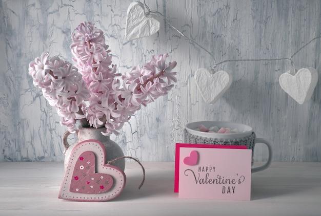 Decoraciones para el día de san valentín, organizador de escritorio blanco con calendario de madera, taza de chocolate caliente y flores de jacinto rosa Foto Premium