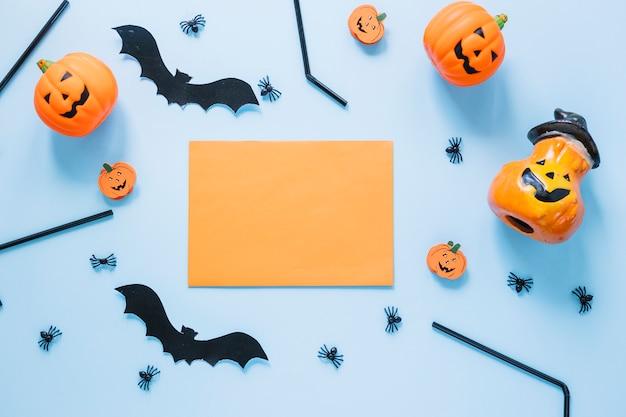 Decoraciones de halloween colocadas alrededor de una hoja de papel en blanco Foto gratis
