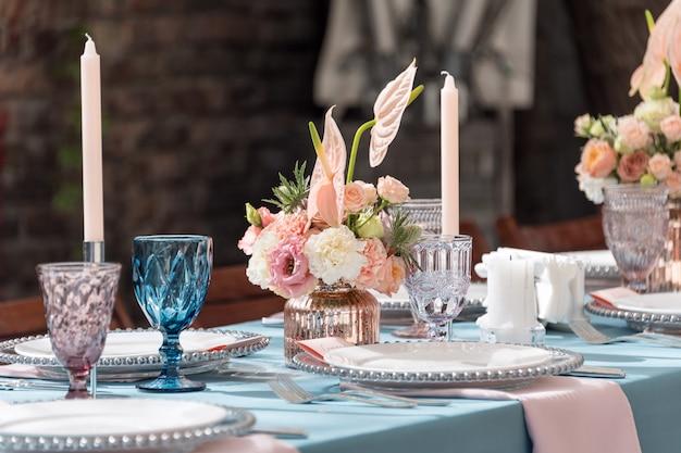 Decoraciones de mesa de flores para fiestas y cenas de boda. juego de mesa para recepción de bodas en restaurante al aire libre. Foto Premium